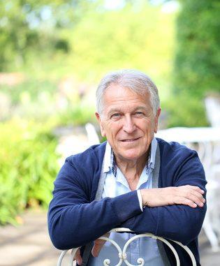 portrait-of-senior-man-sitting-in-home-garden